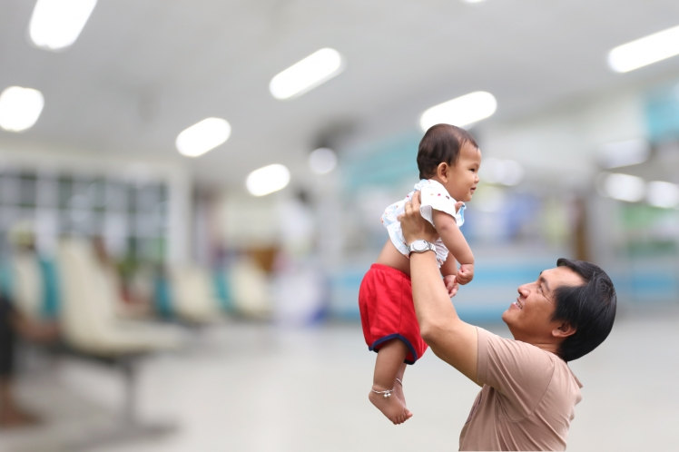 Man håller upp en bebis mot blurrad bakgrund på ett sjukhus. Foto: Mostphotos