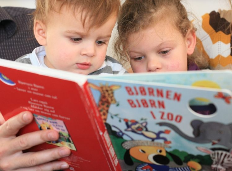 Brother and sister reading a book. Photo: Mostphotos
